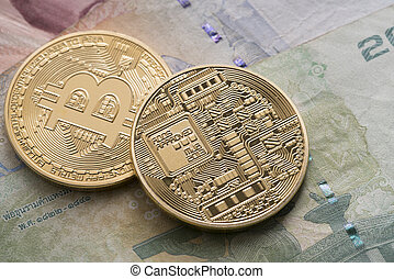 Two golden bitcoin on some bills close up shot