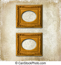 Two golden frames on a grunge wall