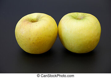 Two golden fresh juicy apples with shadow on dark gray matte background close up view