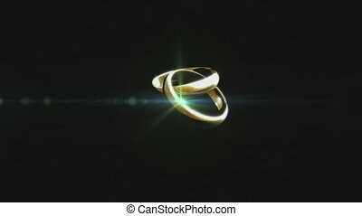 Two golden rings spinning against black background - Digital...