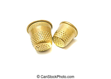 two golden thimbles on white