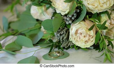 Two golden wedding rings on marble background near flowers...