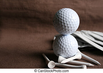 Two golf balls stacked ontop of one another with tees and glove