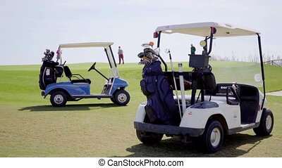 Two golf carts loaded with bags and clubs parked together on...