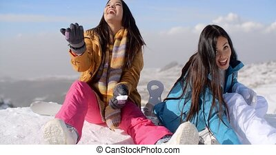 Two gorgeous laughing young woman in snow