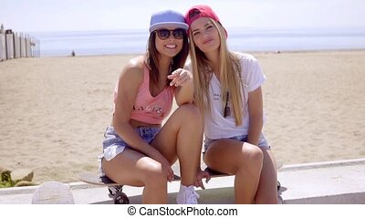 Two gorgeous young women laughing and joking