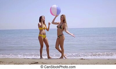 Two gorgeous young women posing with a beach ball