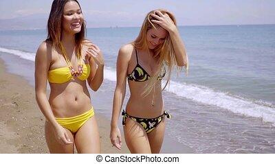 Two gorgeous young women wearing bikinis strolling along the...