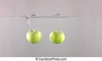 Two green apples fall down in water against gray background,...