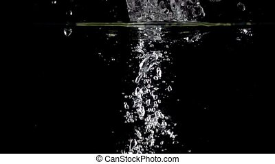 Two green apples fall down in water against black background, super slow motion