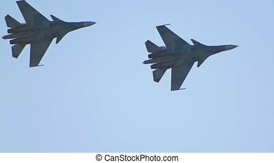 Two green camouflage military fighter jets flying in circles...