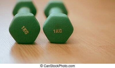Two green dumbbells on the floor