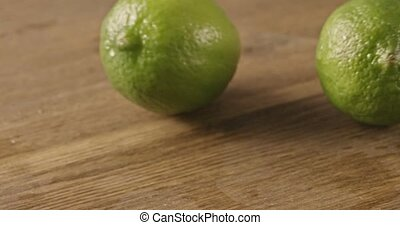 Two green limes roll on a wooden table - Two green limes...