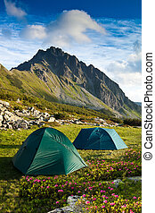 two green tents in the mountains