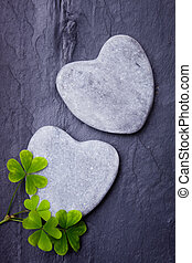 Two grey heart shaped rocks with shamrocks on a tile background