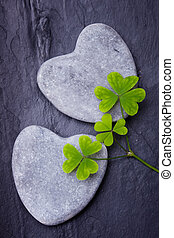 Two grey heart shaped rocks with three clovers on a tile backgro