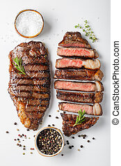 Two grilled marbled beef steaks striploin with spices on ...