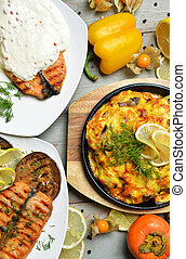 Two grilled salmon fish steaks with white cheese sauce and vegetables