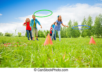 Two group of kids play throwing colorful hoops - Two group ...