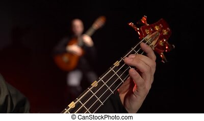 Two guitarists play the bass guitar. Close up. Background...
