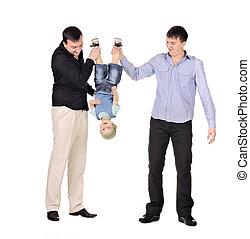 Two gusd holding little boy upside down