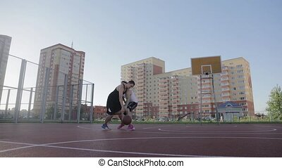 Two guy play basketball at district sports ground in a backlit sun. Shooting with the slider.