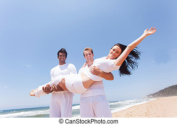 two guys carrying a girl on beach
