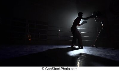 Two guys fight in the ring in the dark - Two guys ight in...
