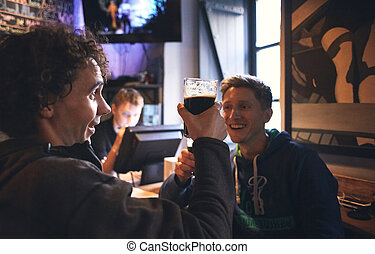 two guys friends sitting in the pub with glasses of beer -...