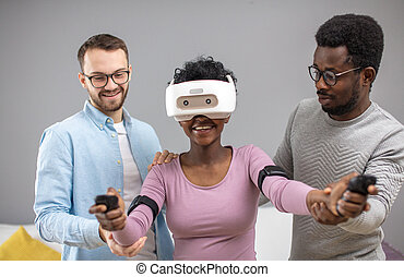 Two guys help african woman trying on virtual reality glasses for the first time