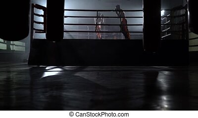 Two guys in the ring fight in the dark ring they...