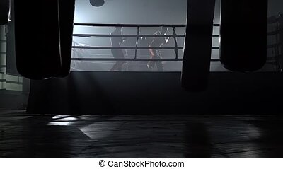 Two guys in the ring fight in the dark. Slow motion - Two...