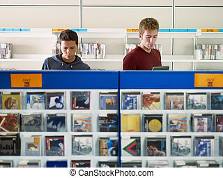 two guys listening music in cd store - two caucasian people...