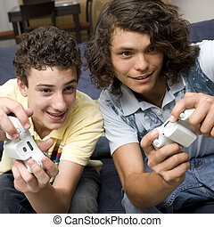 Two guys play videogames on a couch