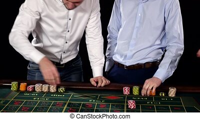 Two guys playing roulette in the casino. Black
