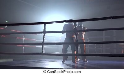 Two guys in the ring fight in the dark they professional kickboxers beat with their feet and hands. Slow motion