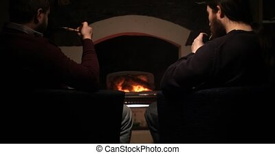 Two guys smoke near the fireplace and drink cognac vape against a classic smoking pipe