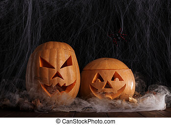 Two halloween pumpkins in spiderweb with spiders and autumn leaves