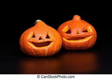 Two Halloween pumpkins on a black background with reflection