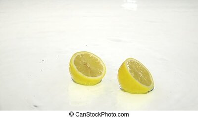Two halves of lemon fall into the water. White background. Slow motion