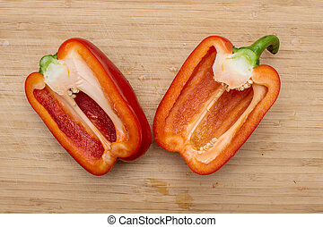 Two halves of red sweet pepper on a wooden background