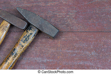 Two hammer on wood background with space for text