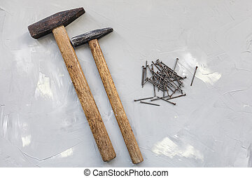Two hammers and old rusty nails on gray background