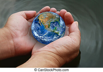 two hand hold the earth on water ,including elements furnished by NASA