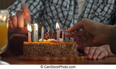 Two hand lighting candles in birthday cake
