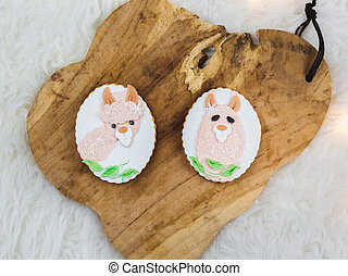 Two hand painted gingerbreads on a wooden background. The ...