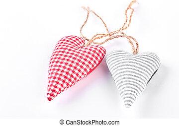 Two handmade fabric hearts.