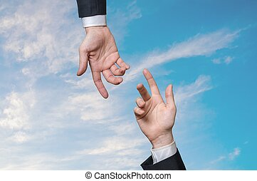 Two hands are reaching each other against blue sky. Help and ass