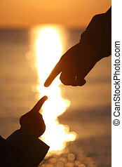 Two hands child and mother touching each other fingers near sunset sea