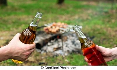 Two hands clink bottles with beer